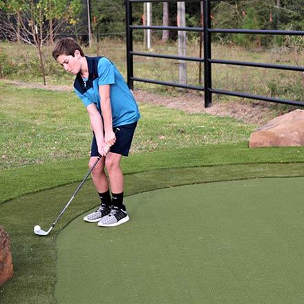 Boy playing golf on SYNLawn Artificial Turf