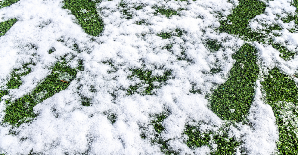 Artificial turf covered in light snow during the winter.