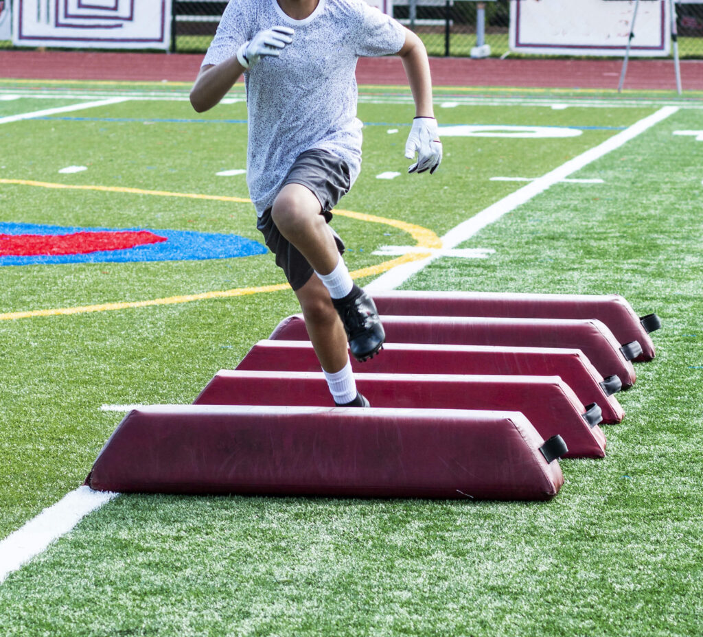 football player practicing on artificial grass
