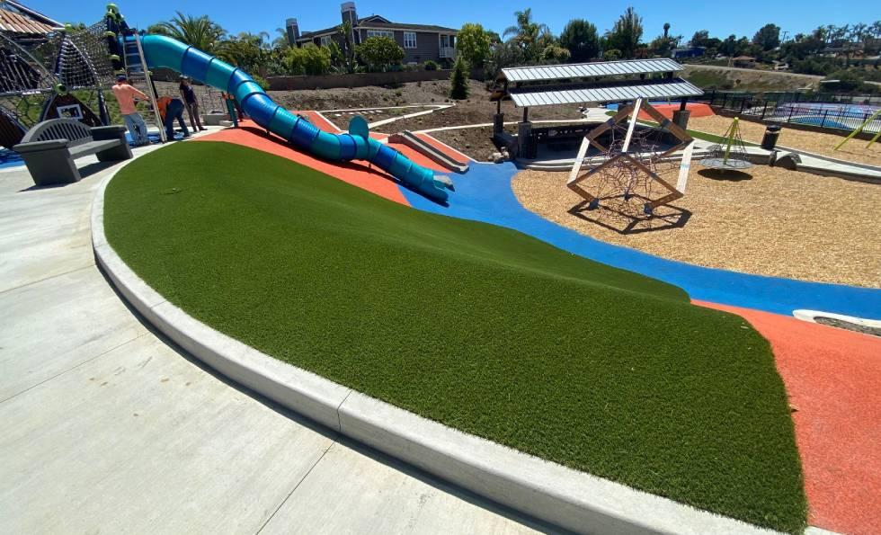 Slide and play area view of the Olympus Park with artificial grass provided by SYNLawn